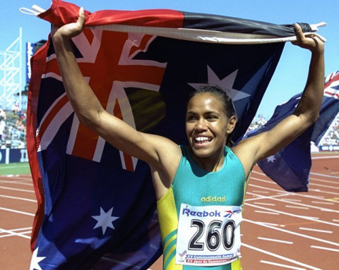 Cathy Freeman carries the Aboriginal and Australian flags on victory laps at Victoria 1994